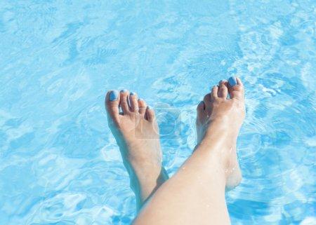 Photo pour Pieds de femme contre l'eau bleue de la piscine - image libre de droit