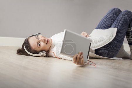Photo pour Joyeux jeune femme avec des écouteurs couchés sur le sol à sa maison, en utilisant une tablette numérique . - image libre de droit