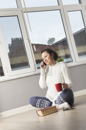 Young woman talking on cellphone while having coffee