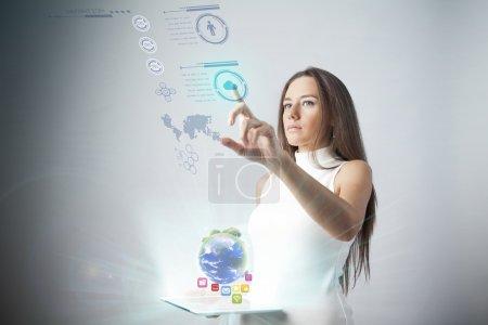 Photo pour Une jeune femme brune vêtue d'une robe blanche high-tech et serrant la main contre un écran holographique - image libre de droit