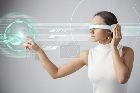 Photo for Young woman with futuristic smart glasses over gray background - Royalty Free Image