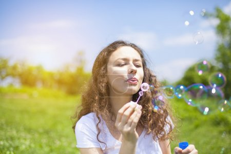 Photo for Young woman having fun and blowing bubbles outdoors. - Royalty Free Image