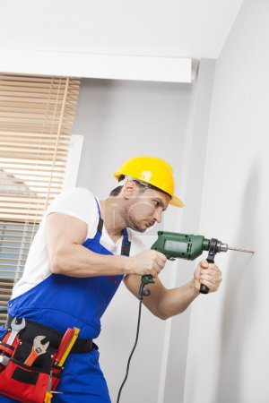 Young man drilling hole in wall