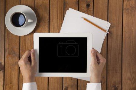 Photo pour Femme d'affaires tenant une tablette pc sur la table en bois - image libre de droit