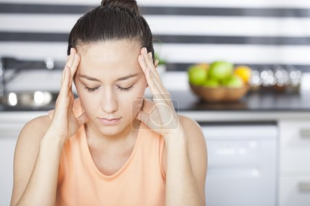 Photo for Stressed young woman in kitchen - Royalty Free Image