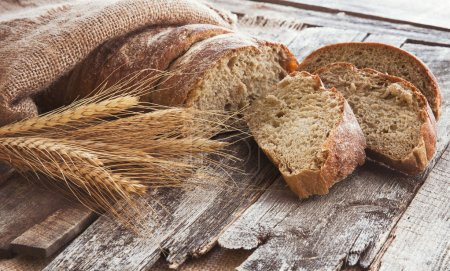 Fresh bread and wheat on the  wooden background. Toned