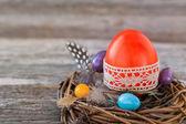 Červené velikonoční vajíčko zdobené krajkou v malé hnízdo na dřevěné pozadí