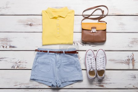 Bright yellow polo shirt and denim shorts.