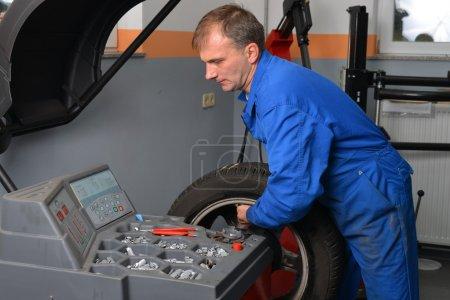 Photo pour Roue d'équilibrage, mécanicien automobile tourne une roue de voiture qu'il attend pour lui dire qu'il a atteint le bon endroit pour ajouter un équilibrer le poids de la machine. - image libre de droit