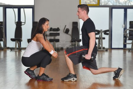 Man working out with female personal instructor