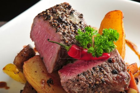 Photo for Juicy steak with baked potatoes and mushrooms - Royalty Free Image