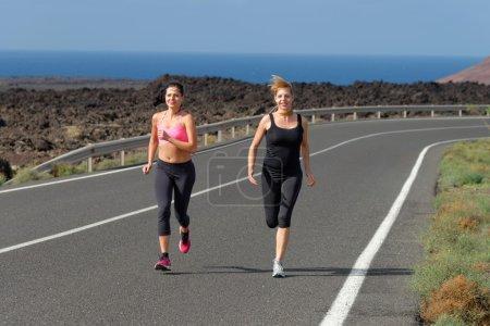 Two Runner women running on mountain road