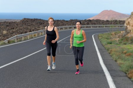 Runner womans running on mountain road in beautiful nature,
