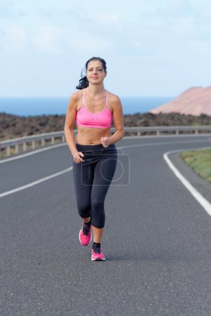 Runner woman running on mountain road in beautiful nature