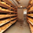 Cow milk cheese, stored in a wooden shelves and le...
