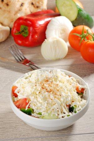 Foto de Ensalada de shopska también conocido como búlgaro, Macedonio, serbio, bosnio y croata Ensalada hecha de tomates, pepinos, cebollas, pimientos crudos o asados, sirene - Imagen libre de derechos