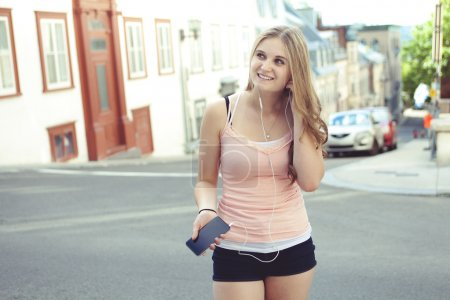 Teen girl listening to the music with earbuds from a smart phone on an urban background