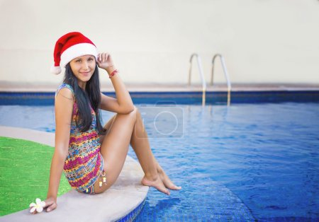 New Year at sea.  New Year next to the pool. Beautiful girl near a swimming pool. Santa