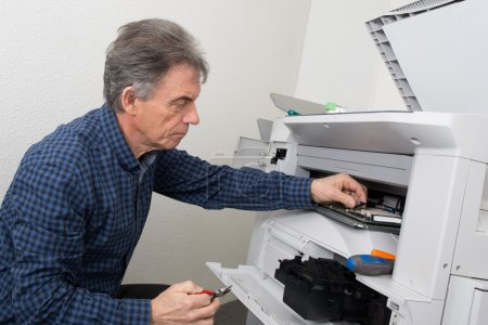 Photo for Closeup shot young male technician repairing digital photocopier machine - Royalty Free Image
