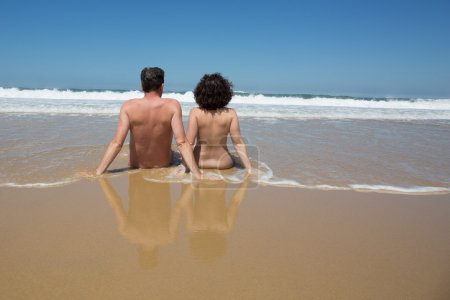 Couple in the water at the beach, backside to camera