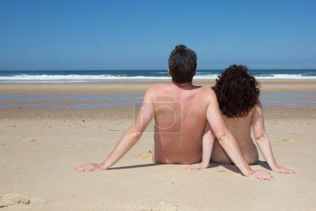 Relaxing nudist couple sitting on beach under deep blue sky