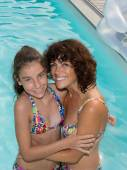 Krásná žena a mladá dívka se koupe v bazénu