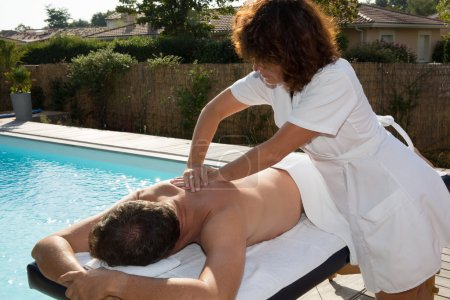 Handsome middle aged man having a massage by the pool