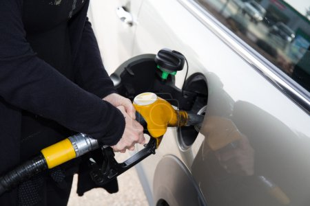 Hands of woman refueling her car