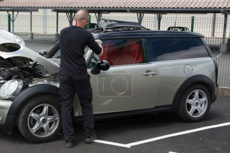 Automobile glazier worker disassembling windshield of a car