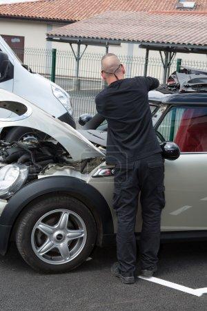 Automobile glazier worker disassembling windshield