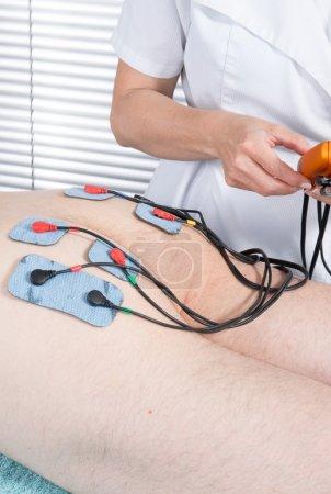 Photo pour Bas haut Angle vue du thérapeute plaçant électrodes sur de l'homme - image libre de droit