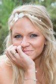 Blonďatá žena ve svatebních šatech na pláži