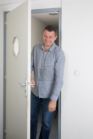 Happy and smiling man at the door