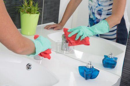 woman is  cleaning a bathroom