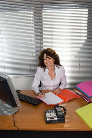 Happy and smiling business woman working in office