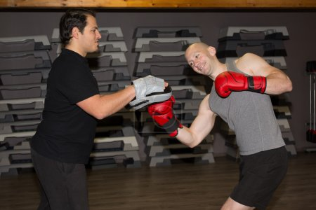 Two caucasian men exercising thai boxing at fitness center