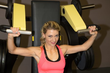 Happy woman exercising on rowing machine in gym