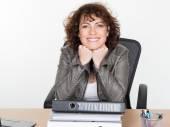 Bruneta úřadu žena pracující, sedící u stolu