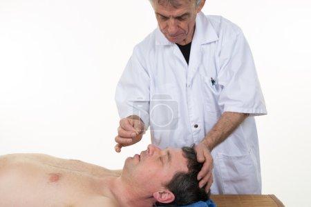 Photo pour Traitement de médecine chinoise - médecin de sexe masculin faisant l'acupuncture - image libre de droit