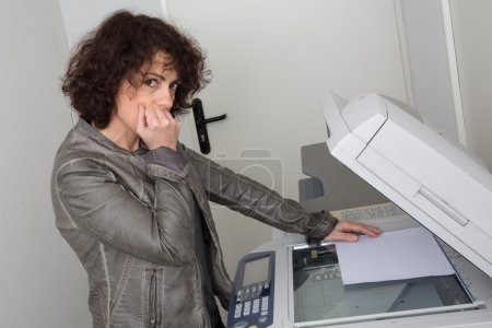 Business woman having trouble with copy machine