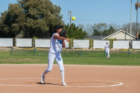 Photo for Filipino softball pitcher throwing the ball to first base. - Royalty Free Image