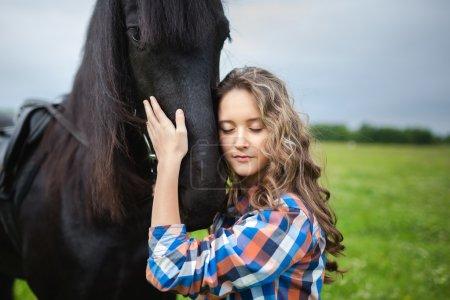 Photo pour Jeune belle fille avec cheval frisien debout dans la prairie à l'heure d'été - image libre de droit