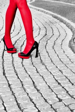 Fashion urban womens legs, heels. Black white, red, paving stone