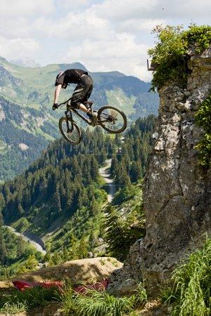 Photo pour Mountainbiker sauter d'un rocher - image libre de droit