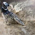 Mountainbiker rides on path in mud...