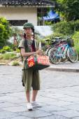Yangshuo, China - circa July 2015: Chinese young pioneer girl sells food or souvenirs on the streets of tourist town Yangshuo on the banks of Li river in  China