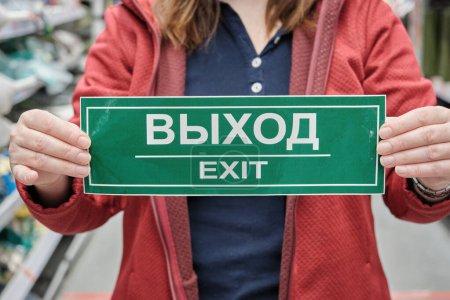 Frau hält Schild mit der Aufschrift Ausgang in Russisch und Englisch. Nahaufnahme