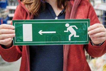 Frau hält Schild mit Notausgang in der Hand. Nahaufnahme mit den Händen