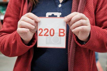 Mädchen hält Schild mit russischem Buchstaben. Label warnt vor 220 Volt elektrischer Spannung