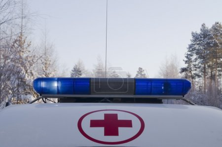 Red cross in the red circle and working blue flashing beacons on the roof of the ambulance